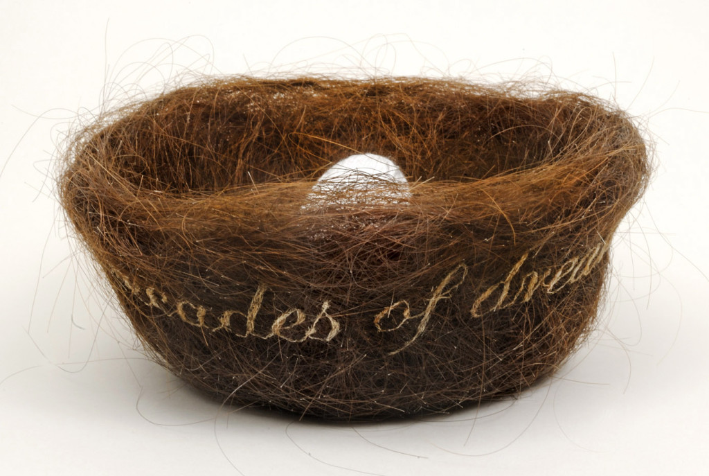"Decades of Dreaming of You 2012, hair embroidery on mother's (artist's) hair from gestation period, thread from unraveled pillowcase wound into egg shape, 3 x 5 x 5"". Text reads ""Decades of Dreaming of You"". Nina Fuentes Collection, Miami."